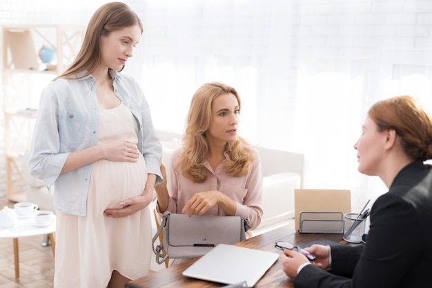 医者のオフィスで妊娠中の娘を持つ母。