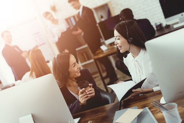 コールセンターの女の子オペレーターは互いに通信します。