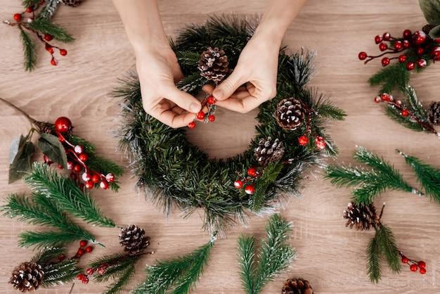 クリスマス休暇のためのクリスマスリースを作る女性。