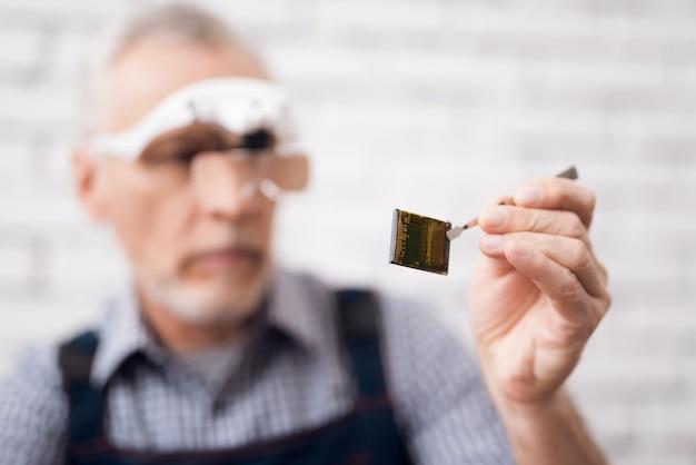 Пожилой мужчина смотрит на процессор через специальные очки.
