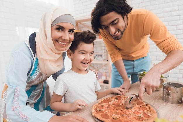 彼の父親と一緒の小さな男の子はピザを切っています。