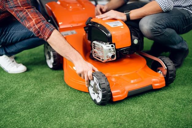 コンサルタントは男と女に芝刈り機を見せる。