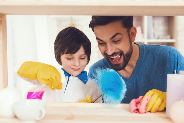 父と息子がほこりから家具の表面を拭く