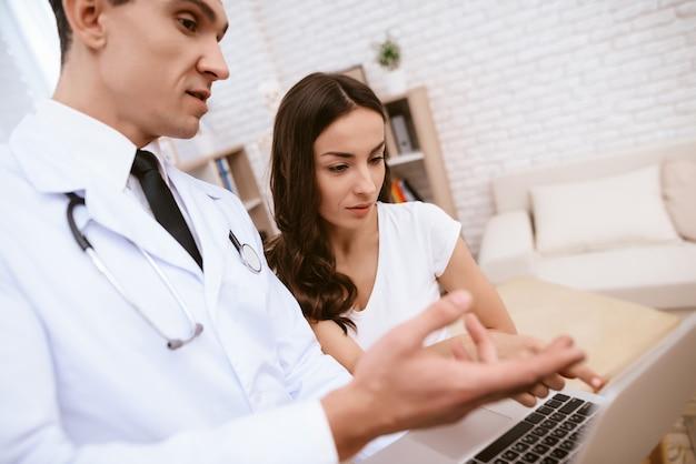 医者は妊娠中の女の子にラップトップ上で何かを見せています。