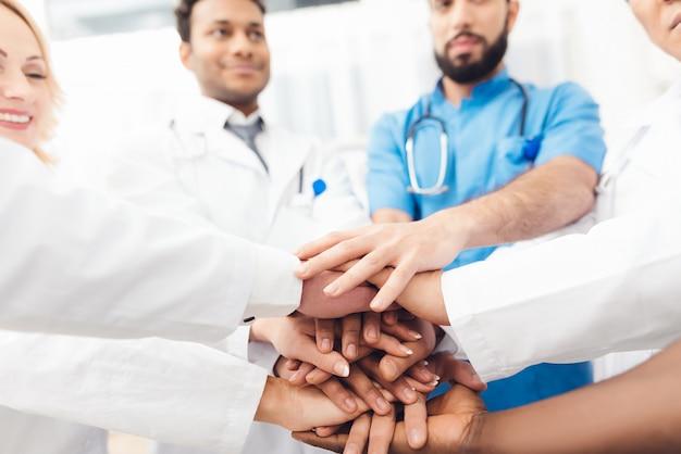 Группа врачей держат друг друга за руки.