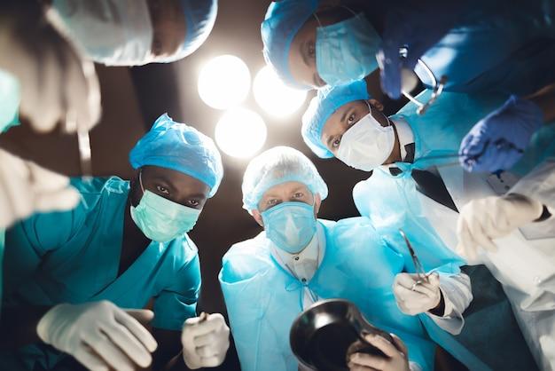 医師は手術台の上に横たわる患者を見ます