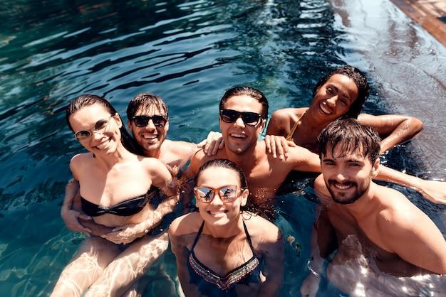 楽しんでサングラスをかけている若い笑顔の人々のグループ