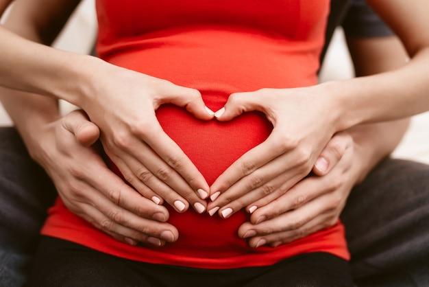 Мужчина обнимает живот своей беременной жены.