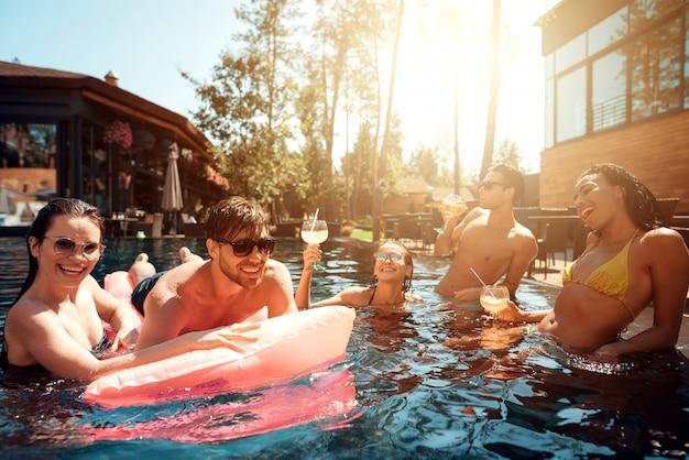 Молодые счастливые люди, плавание в бассейне