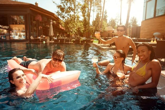 プールで泳いでいる若い幸せな人々のグループ