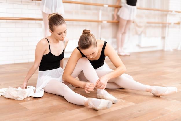若い女の子のバレエダンサーはバレエクラスでリハーサルします。
