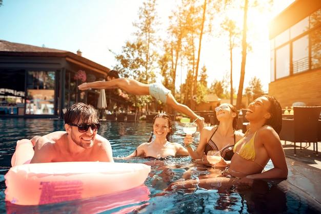 プールで泳いでいる若い幸せな人々