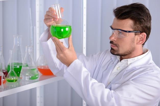 男性医師が彼の手に緑色の液体を保持しています。