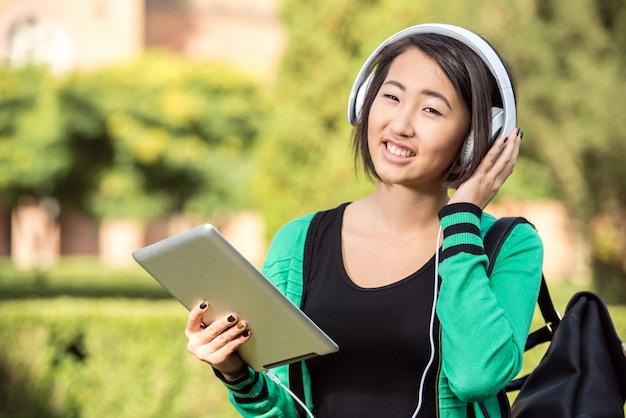 若い笑顔のアジアの女の子はタブレットで音楽を聴いています。