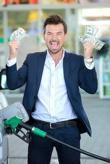 Эмоциональный бизнесмен держат деньги.