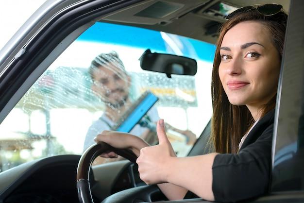 ガソリンスタンドでガソリン車を充填しながら車の窓を洗浄
