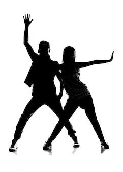 Силуэт пара танцует хип-хоп.