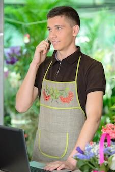 Флорист человек, работающий с цветами в теплице.