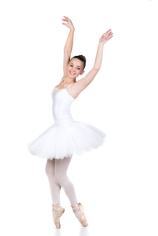 白い部屋で踊る若い美しいバレエダンサー。