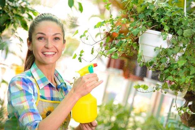 Молодой усмехаясь флорист женщины работая в парнике.