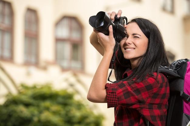 町の若いハンサムな女性は写真を撮っています。