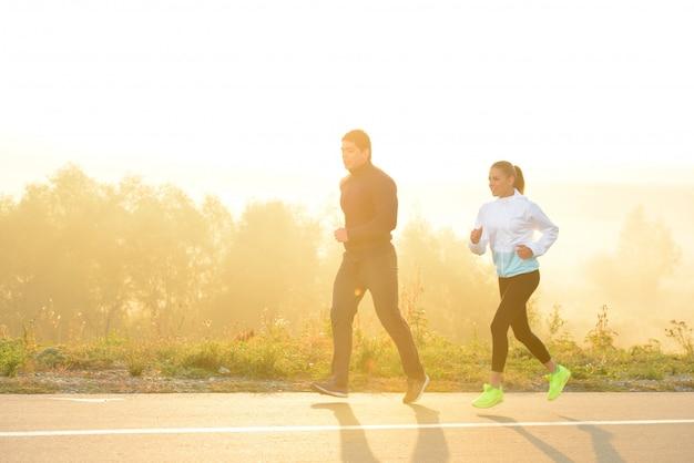 若いカップルが朝公園でジョギングします。