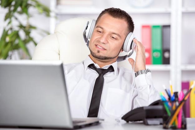 ノートパソコン、テーブルに電話を持つ若い男。