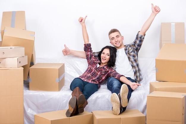 ボックスがたくさんある新しいアパートで幸せなカップル。