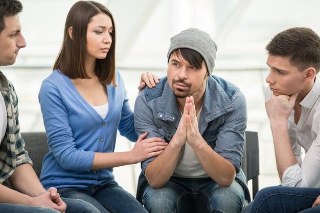 人々は輪になって座り、お互いを支え合っています。