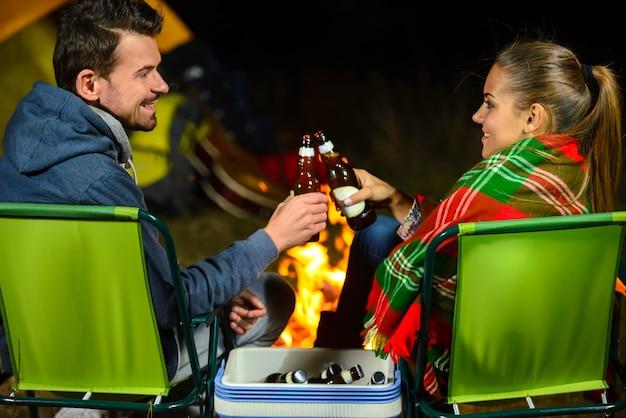 ビールを飲みながらキャンプしながらカップルキャンプファイヤー