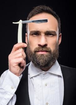 まっすぐなかみそりを持つ若い残忍なひげを生やした男の肖像画。