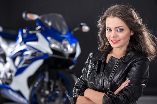 Портрет молодой привлекательной девушки и мотоцикла.