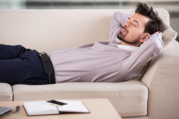 Утомленный бизнесмен спит на софе на офисе.