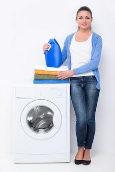 洗剤と洗濯機の近くの洗濯を持つ女性。