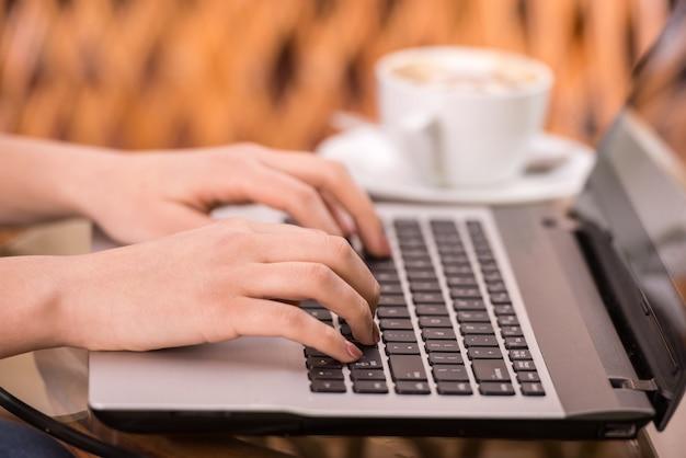 Макро руки молодой женщины использует ноутбук.