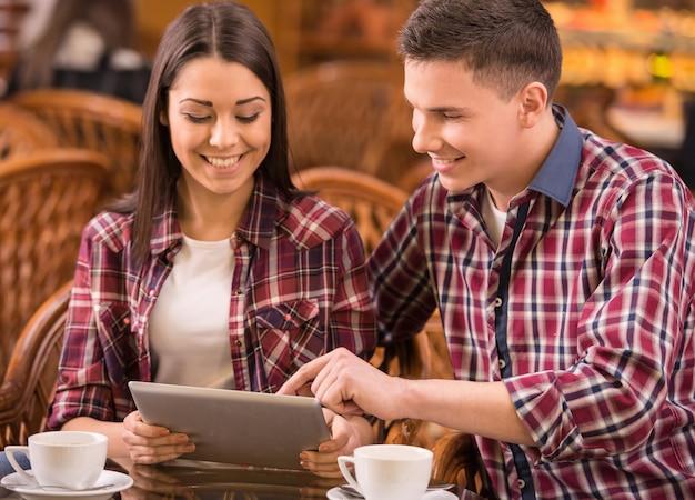 カフェで美しいカップルがタブレットを使用しています。