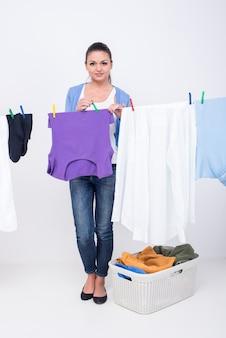 若い女性は物干しに服をぶら下げています。