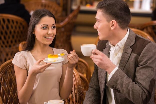 カップルはコーヒーショップでケーキとコーヒーを楽しんでいます。