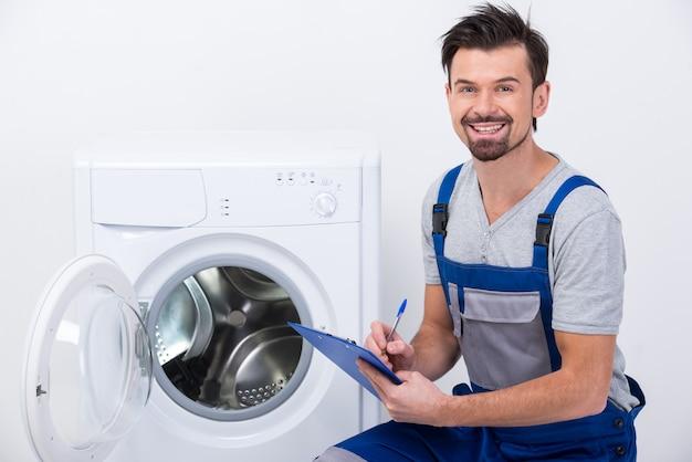 Ремонтник ремонтирует стиральную машину.