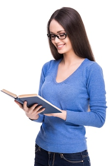 教科書を保持しているメガネでスマート美しい学生少女。