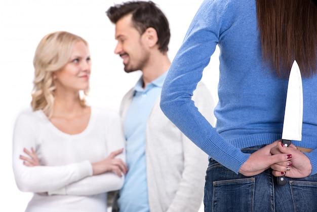 若い笑顔のカップルとそれらを見てナイフを持つ女性。