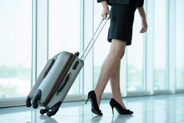 Деловая женщина путешествует с тележкой.
