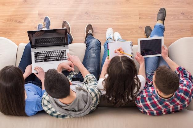 学生はラップトップでソファーに座っています。