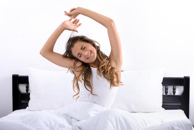 彼女の寝室で、完全に休んで目を覚ます女性