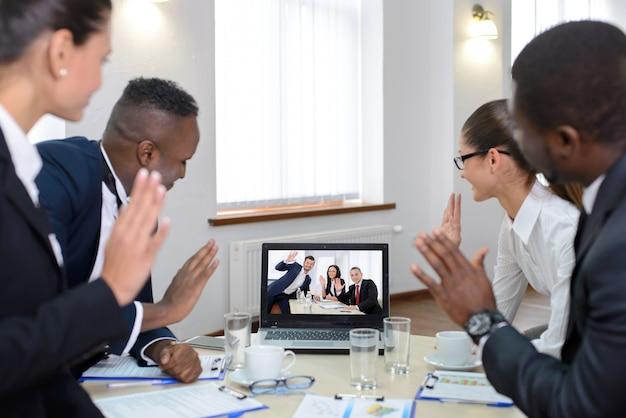 人々はコンピューターの画面でオンライン会議を見ています。