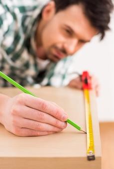 Человек измеряет деревянную доску с измерительной ленты.