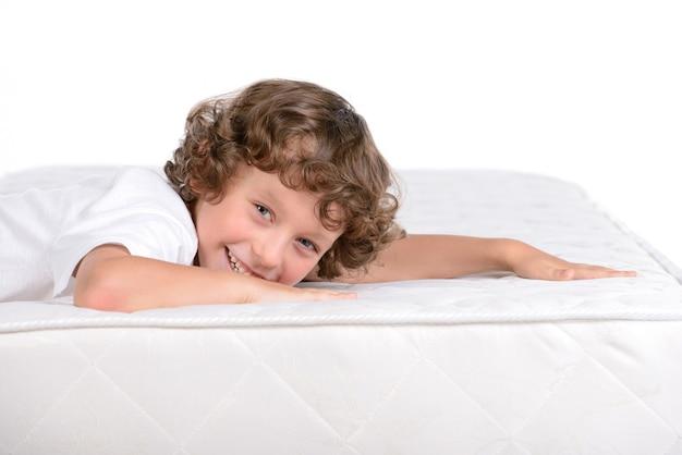 その少年はマットレスの上に横になっていて笑っています。