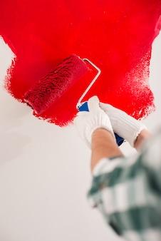 Конец-вверх руки с роликом красит стену в красном цвете.