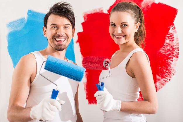 Пары делают ремонт дома и красят стену.