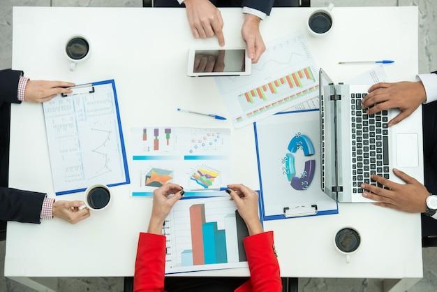 ビジネスの人々の手はドキュメントを使って作業しています。